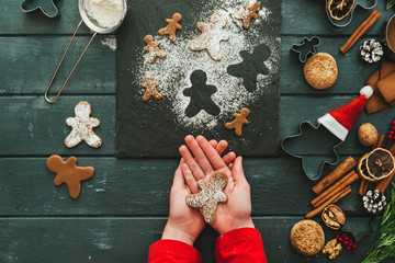 Girl holding gingerbread man with ingredients on table