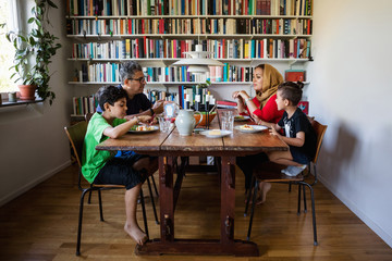 Family having meal at table by bookshelf