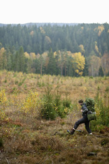 Side view of male hiker walking on field during autumn