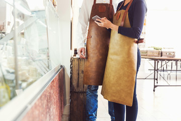 Midsection of owners using digital tablet in grocery store