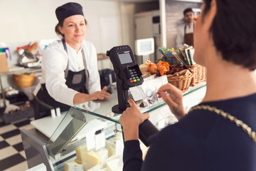 Saleswoman looking at female customer entering pin in credit card reader at grocery store