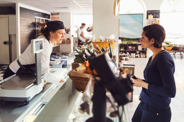 Side view of woman talking to saleswoman at counter at grocery store