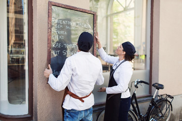 Male and female owners putting blackboard on wall outside grocery store
