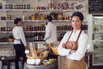Portrait of confident owner standing arms crossed while colleagues working in grocery store