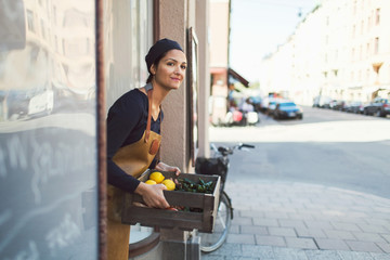 Smiling female owner carrying vegetable crate at entrance of grocery store