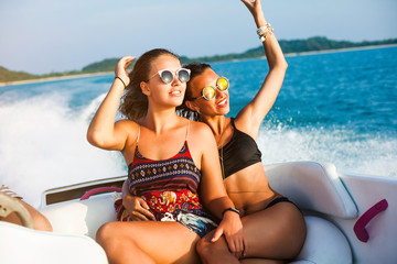 Two pretty amazing hipster girls, blond and brunette ride on a speed boat, wearing sunglasses, happy, tanned, crazy emotions, sexy bikini, fashion accessories fashion, luxury, lifestyle waves splashes