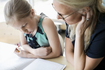 High angle view of girl with teacher at classroom