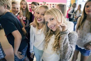Portrait of happy schoolgirl showing peace sign with friends in corridor