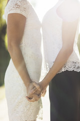 Midsection of newlywed lesbian couple holding hands