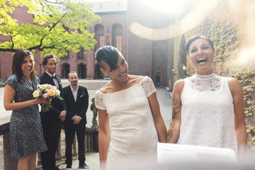 Cheerful lesbian couple and guest laughing during ceremony