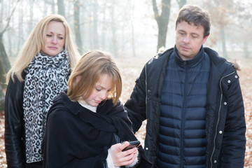 sad mother and father with blond daughter with phone in park