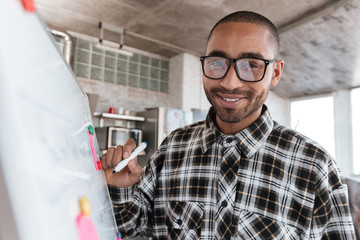African cheerful businessman wearing glasses in office working with flipchart