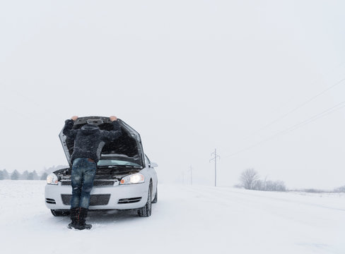 Rear view of man looking under hood of broken down car on snow covered landscape