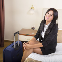 Smiling young business woman relaxing in her hotel room. Wine glass by her side.