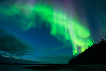 Aurora on Lake - Bright cloud-shape aurora borealis beam down over a lake from the starry night sky.