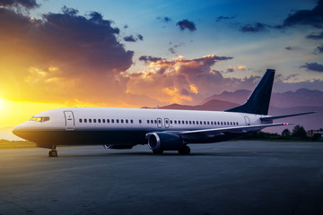 Passenger airplane in airport at beautiful sunset