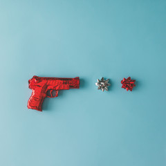 Gun wrapped in red paper with bows on blue background. Flat lay