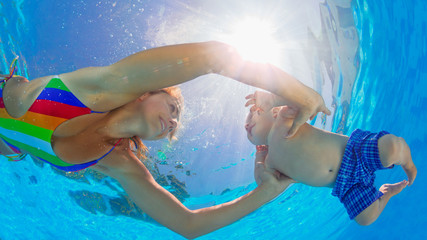Happy family has fun. Underwater photo. Mother teach to swim and dive baby son in swimming pool. Healthy lifestyle, active parent, people water sport and lessons on beach summer holiday with child.