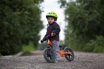 Child in helmet ride balance bike (run bike)