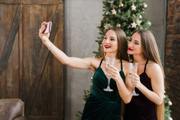 Twins celebrating New Year. Beautiful smiling sisters in evening dresses drink champagne and make selfie on smartphone over Christmas tree. Winter holidays, celebration, people and friendship concept.