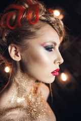 portrait of a beautiful girl with bright make-up with gold glitter