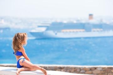 Adorable little girl background big liner in Mediterranean sea