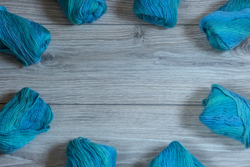 Blue skeins of yarn are beautifully arranged on a wooden background in a circle shape.