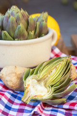 Ripe organic artichokes with lemon and ginger in ceramic bowl on the rustic wooden lattice