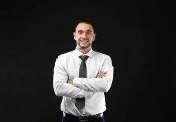 Young business coach with crossed hands standing on black background