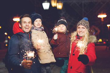 Beautiful family with burning sparklers