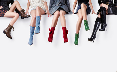 Many colorful boots women sitting together on the white bench. Woman shoes collection.