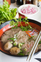 A bowl of traditional vietnamese beef and chicken pho street food, surrounded by fresh herbs. Pho is a vietnamese noodle soup consisting of meat, herbs, chilli, coriander and dumplings.