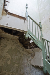 An old rotten broken wooden staircase that has been left to rot in an abandoned building. Stairs are un safe and are a health and safety risk.