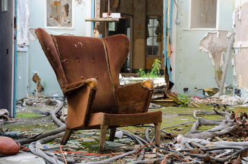 An old worn and damaged armchair, that has been left to rot in an abandoned building amongst concrete debris.