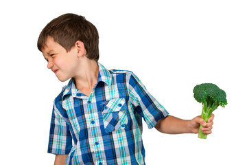 Young Boy Turning his Head away from a Broccoli Bunch