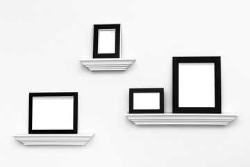 Multiple Blank picture frames on Ledges on a wall