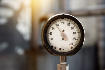 Closeup of industrial manometer measuring gas pressure on the plant. Power generation pipes and valves on the blurred background.