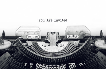 Vintage typewriter on white background with text you are invited