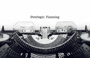 Vintage typewriter on white background with text Strategic Planning