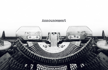 Vintage typewriter on white background with text Announcement.