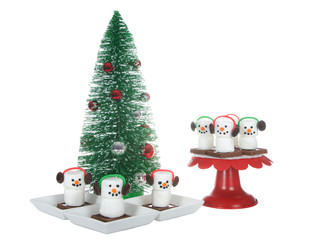Marshmallow s'more men with ear muffs sitting on a chocolate bar square. Festive Christmas holiday snacks served on pedestal next to a miniature tree