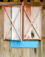 old red aged wooden framed window with blank empty blue label sign