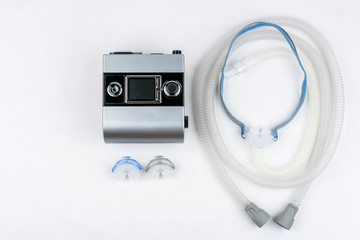 CPAP machine with hose and mask for nose. Treatment for people with sleep apnea, respiratory, or breathing disorder. Shot from above.
