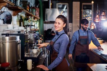 Girl barista bartender waiter in uniform making coffee at the bar
