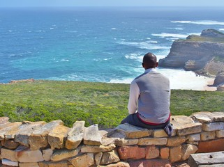 Contemplative African young man sitting on the rocks, looking at distance to the blue sea and thinking about something. The Cape Point in South Africa as a background.