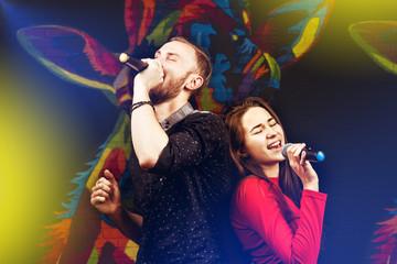 Happy couple singing karaoke club