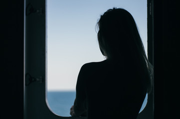 Thinking girl looking on the sea from ferry boat window