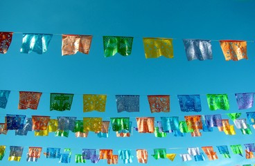 Traditional mexican paper bunting decoration celebratory flags against blue sky