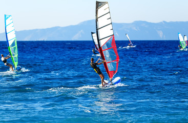 Side view of young windsurfer on background with other windsurfers