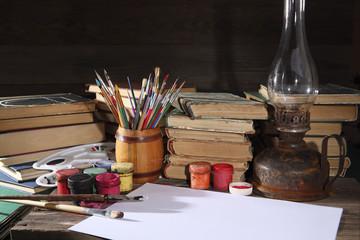 Acrylic paints, easel, artist brush, books and old kerosene lamp on the desktop. Retro still life